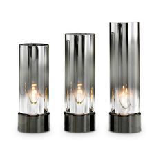 "Unique glass cylinders mesmerize with a dazzling light show. Set includes one of each height: 7 1/2"" h, 8 1/2"" h, 9 1/2"" h; 3"" dia. Metal base. Use with tealights, sold separately.  Price:  $75.00/set of 3"