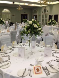 Stunning wedding arrangements of White flowers on martini vases created by Lily White florist