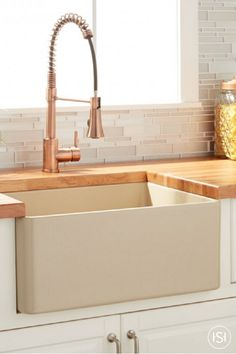 """It's time to give your kitchen a facelift. With inspiration around every corner, this 24"""" Reinhard Fireclay Farmhouse Sink in beige will give your cooking space a family-friendly feel when paired with fresh cabinetry, butcherblock wood countertops, and a copper faucet."""
