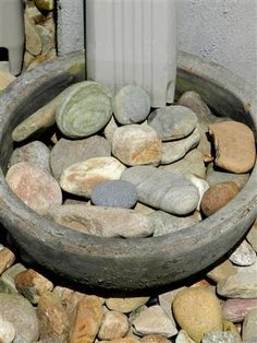 Iead for unsightly rain down spout.  Fill a shallow planter with decorative rocks and have a drain hose from the center hole in the planter out into the garden.  Works great!