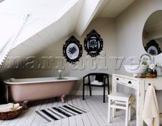 Attic bathroom with metal picture frames and slanted ceiling