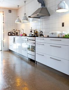 concrete floor with white kitchen and black benchtop