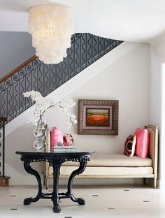 a daybed in the entry, a small piece of art, a capiz shell chandelier, and iron details in the railing.