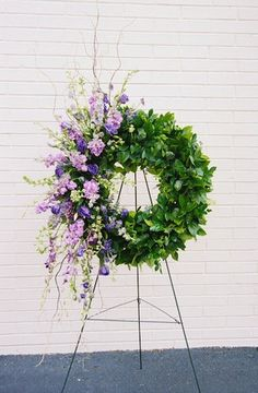This unique funeral wreath pairs the elegance and show of long lavender flowers with the simplicity of green foliage.