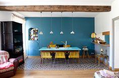 Waouuh, la totale! Mur bleu canard + jaune en touches déco + carreau de ciment/parquet Bright boho-eclectic dining space. Striking teal wall, pops of yellow funky tiles.