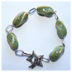 R21 - Pulseira com peças cerâmicas em tons de verde e castanho e forma ondulada.  Elos metálicos e fecho metálico com uma estrela e lua.