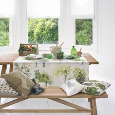 A simple bench packed with pretty accessories and draped in leaf print fabric is ideal for creating a pretty, rustic look in your conservatory.