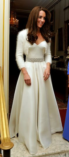 For private wedding reception hosted by Prince Charles, Princess Kate Middleton changed into another dress by Sarah Burton of Alexander McQueen. Her second frock of the day is a beautiful white strapless satin gazar gown with silver diamante embellishment at the waist and a circle skirt. The bride paired it with a cropped angora sweater.