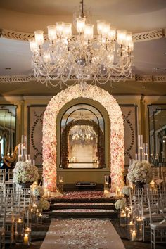 """An elegant New York City ballroom housed the couple's lavish ceremony. A floral arch composed of ivory and blush roses marked the entrance to the space, and an aisle runner sprinkled with rose petals was lined with """"floating"""" candles in hurricane vases. Photography: Michael Falco for Christian Oth Studio. Read More:  http://www.insideweddings.com/weddings/formal-manhattan-wedding-with-opulent-ballroom-decor/517/"""