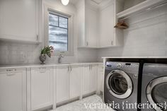 Fabulous laundry room with white shaker cabinets paired with polished nickel cabinet pulls alongside marble counters with a pale gray subway tiled backsplash.
