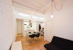 Total white per uno spazio di 40 mq: la muratura in mattoni, le travi a vista del soffitto, gli arredi della cucina e il macroarredo polifunzionale