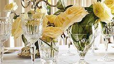 Rosas blancas en la cristalería de mesa, alternando copas y vasos. Un detalle floral que da armonía a cualquier almuerzo. Detrás, un candelabro de plata sube el nivel decorativo.