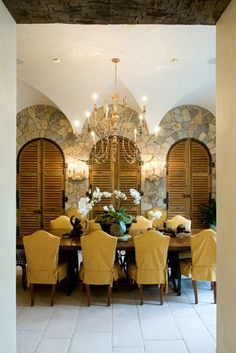 Dining space w/ vaulted ceiling, stone arches, and louvered doors...wine storage behind those doors would be awesome...