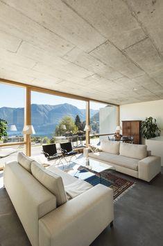 Beton-Deckenplatten haben den Effekt der moderne, die für ein offenes Wohnzimmer mit Boden bis zur Decke Panoramafenstern und einem gedämpften Farbschema perfekt ist.