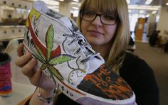 """Jennifer Thammavong, an art therapist from Rockford, Ill,. checks out the work of a client who who had substance abuse issues. Her teen substance abuse treatment center has brought its traveling art exhibit """" n My Shoes"""" to the Milwaukee Central Library for the month of April."""