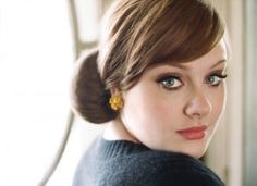 Adele sporting a 1950s hair style and wearing a jumper and jeans in this portrait