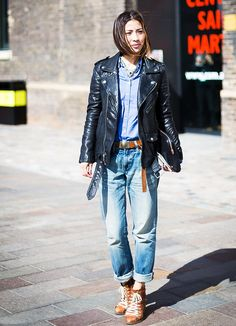 A blue button-down is paired with a leather jacket, belted boyfriend jeans, and lace-up boots