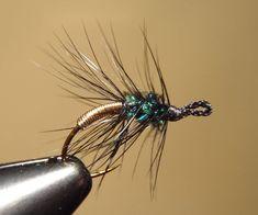 Recipe:  Peacock & Gold  Hook:  Any eyeless hook  Thread:  Black 8/0  Eye:  #2 silk bead cord, black  Abdomen:  Gold wire, med.  Thorax:  Peacock sword  Hackle:  Black saddle