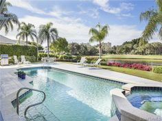 Pretty backyard pool with lake view and high rises in the distance.  Barrington Pelican Bay - Naples, Florida