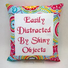 This is a funny cross stitch pillow done in pink. It measures roughly 10 x 11 inches in size at the outside dimensions. The stitching is done on