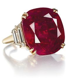 Jewels for Hope: The Collection of Mrs Lily Safra - ENLARGED - A RUBY AND DIAMOND RING, BY CHAUMET -   Set with a cushion-shaped ruby, weighing approximately 32.08 carats, to the trapeze-cut diamond shoulders, with French assay mark for gold.  The 32.08 carat cushion-shaped Burmese ruby, formerly in the collection of Luz Mila Patiño Rodríguez, Countess du Boisrouvray. Price realized $6,736,750