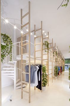Clothes hang from wooden ladders in Mit Mat Mama store by Román Izquierdo…