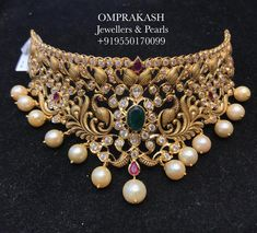 Presenting the beautiful handmade nakshi choker! Designed Handcrafted by Experts...Beautiful necklace with dancing peacock design. Necklace having pearl hangings. Necklace studded with kundans and emeralds.