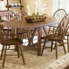 "Farmhouse-style dining table with a weathered oak finish and 2 extendable leaves. Product: Dining table    Construction Material: Select hardwoods, pine and knotty oak    Color: Weathered oak     Features:  Weathered rustic surfaces   Includes two 18"" leaves      Dimensions:  Without Leaves: 30"" H x 66"" W x 40"" DWith Leaves: 30"" H x 102"" W x 40"" D   Note: Chairs not included"
