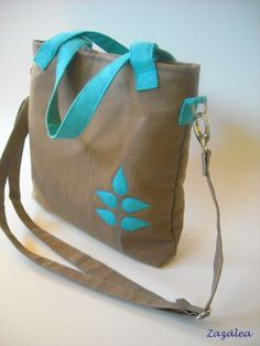 Brown shoulder bag with turquoise handle and motif.