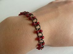 Black and red bracelet -- great newbie project as it's easy and you get to practice opening and closing jump rings correctly. Vary by adding one bead per ring, add beads to every ring instead of every other, change bead shape (e.g. drops, rizo) etc.
