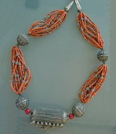 Necklace from the Yemen silversmiths of Ethiopia. | The center bead called a Kutub, and the Round beads called flower Bawsani beads (with a hallmark form the silversmith), mixed with mediterranean coral and small silver beads.  Circa late 19th Century.