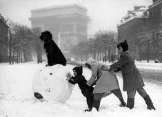 Paris sous la neige Paris en 1930 – Des enfants (et un chien) jouent avec la neige, près de l'Arc de Triomphe. On apprécie la belle performance !