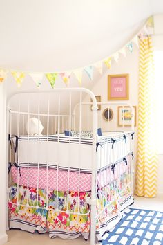 lovely mix of colors in a girls nursery. Love the eclectic mix of fabrics and bright colors!
