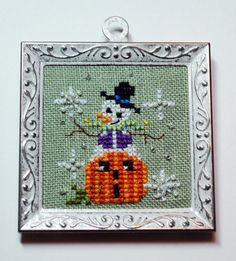 this cute little tree ornament hand cross stitched displays a snowman sitting on top of a pumpkin size is x framed ornament and frame