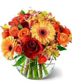 Lush Leonidas Roses, orange spray roses, golden gerbera daisies, and peach Peruvian Lilies