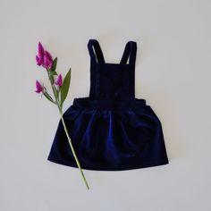 Klassisch, zeitlos mit einem Hauch Vintage. Der verwendete Samt verwandelt diesen minimalistischen Schnitt in ein sehr edles Kleidungsstück. Im Rücken ist das Kleid mit einem Gummizug versehen. die Träger sind mit zwei Knopflöchern angefertigt, damit es in der Grösse verstellbar ist und mitwachsen kann.
