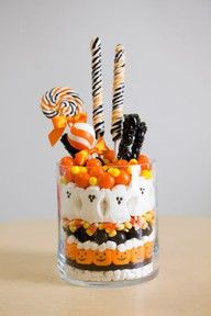 centerpiece - layered mini marshmallows, black licorice, pumpkin Peeps, more mini marshmallows, large black gumballs, candy corns, ghost Peeps, large orange gumballs and mini yellow gumballs. She stuck a variety of lollipops into the top. Mini marshmallows were used as filler inside the jar.