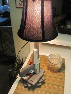 I decided to use some extra NES games and parts to create the most epic lamp. I used an old table lamp, rewired through a gutted Zapper, and used game cartridges as the base. Best part - the trigger actually turns on and off the lamp.