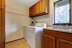 This is a modern laundry room with good sized sink, cupboards and a drying hanger