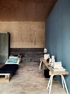 Plywood wraps down to hover above the ground plane and a simple concrete floor.