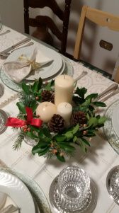 Centrotavola con candele avorio di diversa grandezza con erbe invernali, nastro rosso e pigne su un alzatina di cristallo