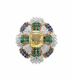 A DIAMOND, YELLOW SAPPHIRE, EMERALD AND SAPPHIRE BROOCH, BY DAVID WEBB  -   Set with a detachable modified octagonal-cut yellow sapphire, within a two-tiered circular-cut diamond, emerald and sapphire surround with sculpted gold detail, mounted in gold and platinum, with pendant hook for suspension, circa 1965.