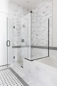 Beside a marble clad drop-in bathtub, a seamless glass shower fitted with an oil rubbed bronze door handle boasts an oil rubbed bronze shower head mounted against gray marble subway wall tiles accented with black greek key border tiles.