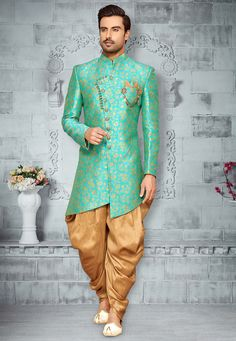 Art Silk Jacquard Asymmetric Sherwani in Turquoise This Readymade attire is Enhanced with Buttons and is Crafted in Chinese Collar Neck and Full Sleeve Available with an Art Silk Dhoti in Beige Do note: Brooch and Footwear shown in the image is for presentation purposes only. Half to one inch may vary in measurement. (Slight variation in actual color vs. image is possible)