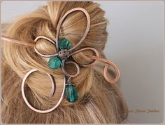 A curly copper hair pin with 2 emerald green faceted glass beads and matching drop which swings freely. This hair slide is made from pure