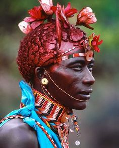 A Samburu warrior from Kenya is expected to be strong, noble and courageous in character, but being Samburu also means he will spend many hours at a time grooming himself. Highly sought after French silk roses, traded in the market have become the piece de résistance of a warrior's striking coiffure today. 2004 #photography #carolbeckwith #angelafisher #samburu #kenya