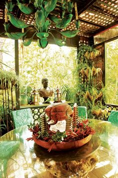 The treehouse pavilion is filled with classic Duquette—his Palmer chairs covered in a malachite print, plant stands made from cast clamshells, and a metal chandelier Duquette designed for Elizabeth Arden.