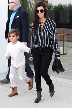 Kourtney Kardashian wearing Saint Laurent Wyatt Leather Chelsea Boots, The Row Round-Frame Acetate and Metal Sunglasses, Faithfull The Brand Stevie Tilbury Stripe Shirt, Chanel Dallas Lambskin Leather Drawstring Fringe Bag