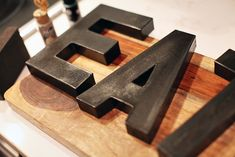 How to make paper mache letters from Hobby Lobby look like weathered metal with oil-rubbed bronze spray paint, gold and black acrylic craft paint and satin finish polyurethane
