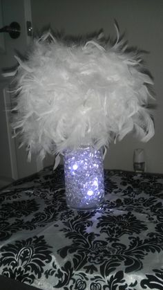 All she did was wrap 2 feather boa around the foam ball and used the pins to hold it down as she went around the ball. Used 2 so it can be fuller and larger. Hot glued the silver ribbon around the top base of the vase. You really can't see in the pictures but figure it will be an added detail to see at the table. found on Weddingbee.com